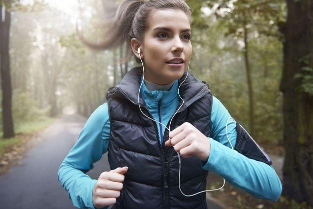 Frau joggt im Wald mit Kopfhoerern Ratgeber: Welche Kopfhörer sollte ich kaufen?