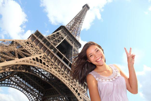 Eine fröhliche Frau posiert vor dem Eifelturm.