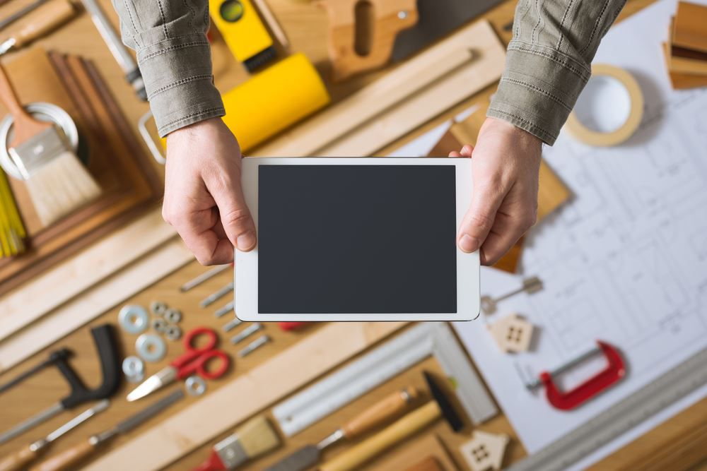 Mann hält ein Tablet im Hintergrund Werkzeugbank mit Werkzeug Der große Smart Home Ratgeber