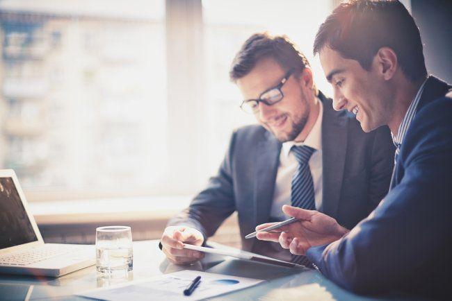 Zwei junge Männer im Anzug bei einer Besprechung Kaufmännische Berufe: Der etwas andere Leitfaden