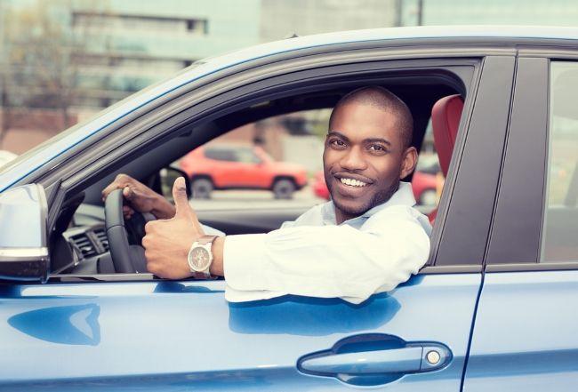 Junger Mann voller Freude in seinem BMW So sparst du richtig beim Autokauf – der große Ratgeber zum Thema Autokauf