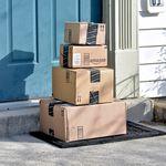 """Das Bild zeigt vier übereinandergestapelte, kleiner werdende Pakete mit der Aufschrift """"Amazon"""", die vor einer Haustür liegen."""