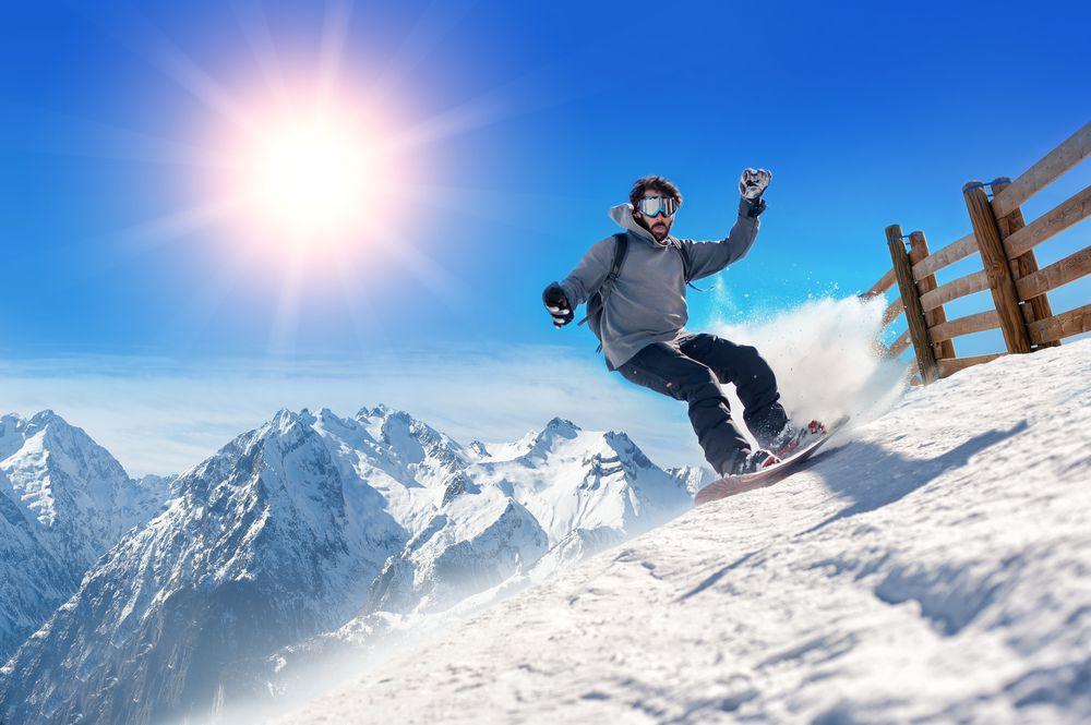 Snowboarder vor schönem Panorama Skiurlaub in den Alpen – So spart man richtig viel Geld!