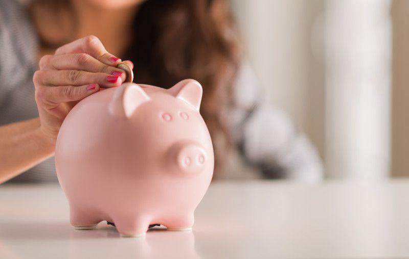 Frau wirft Münze in Sparschwein