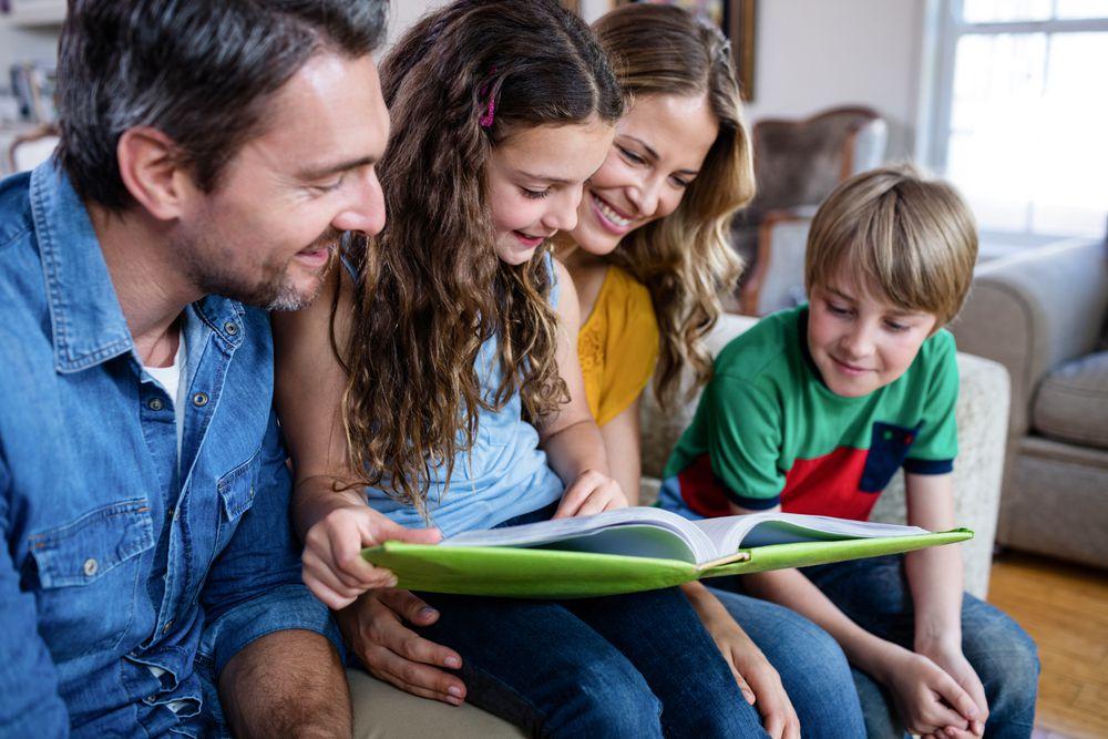 Familie schaut gemeinsam das neue Fotobuch an!
