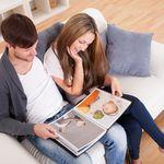 Glückliches Pärchen auf dem Sofa blättert durch ein Fotobuch!